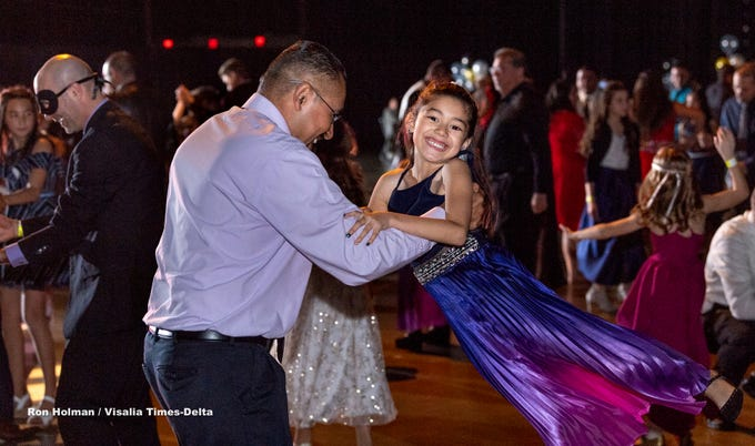 """Venancio Lopez swings his daughter Mila Lopez, 6, during the annual Father-Daughter Dance at the Visalia Convention Center on Saturday, February 16, 2019. This year's theme was """"Masquerade Ball,"""" and included music, dancing and refreshments."""