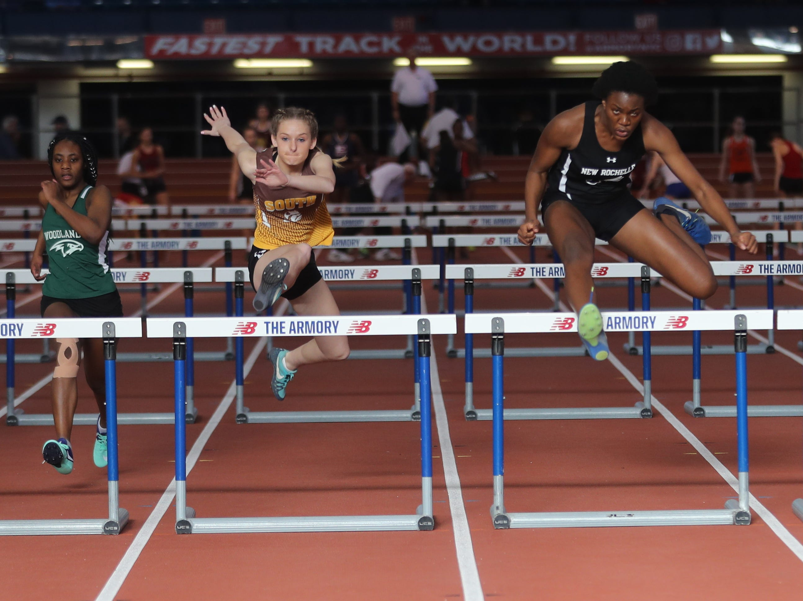 Athletes compete in the 55 meter hurdles during the Section 1 New York State Track and Field State Qualifier at the New Balance Armory in Manhattan Feb. 17, 2019.