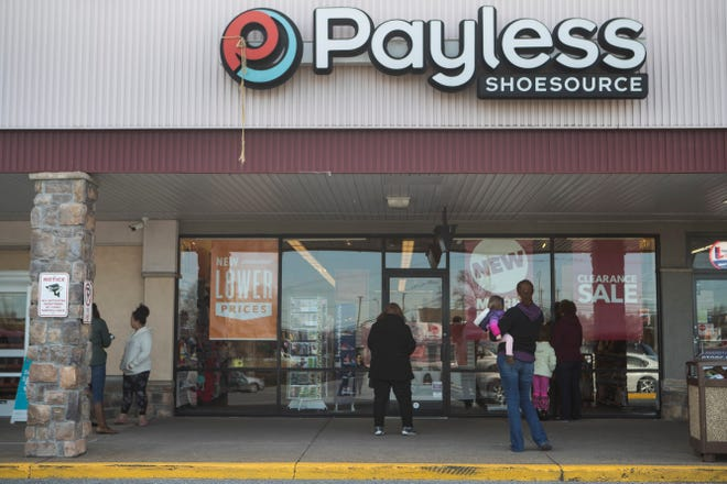 People wait outside Payless ShoeSource before the company's liquidation sale begins Sunday morning in Newark. Payless ShoeSource confirmed Friday that it will close its 2,100 stores in the U.S. and Puerto Rico and start liquidation sales Sunday.