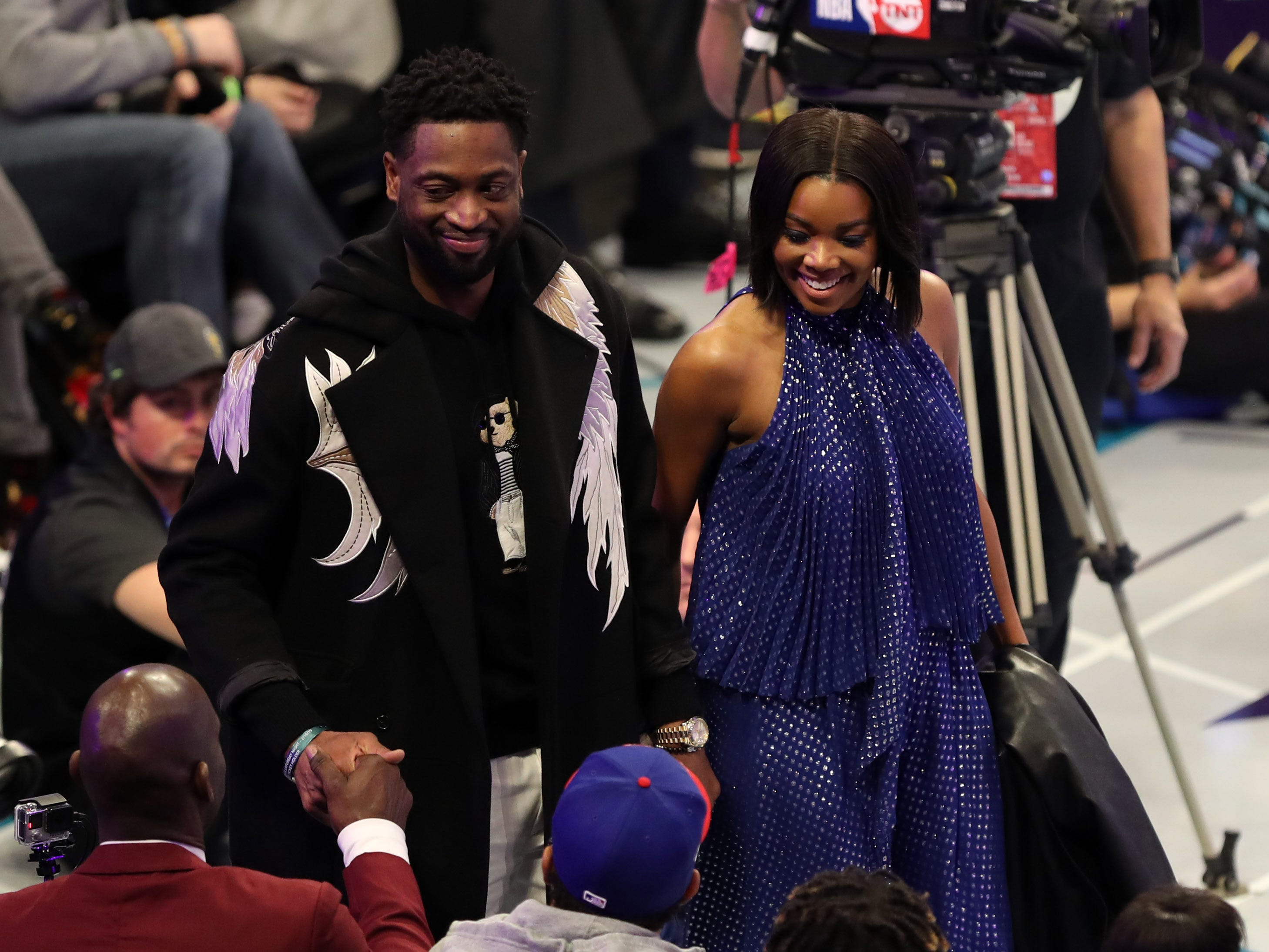 Dwyane Wade and wife Gabrielle Union-Wade walk on to the court during NBA All-Star Saturday Night.
