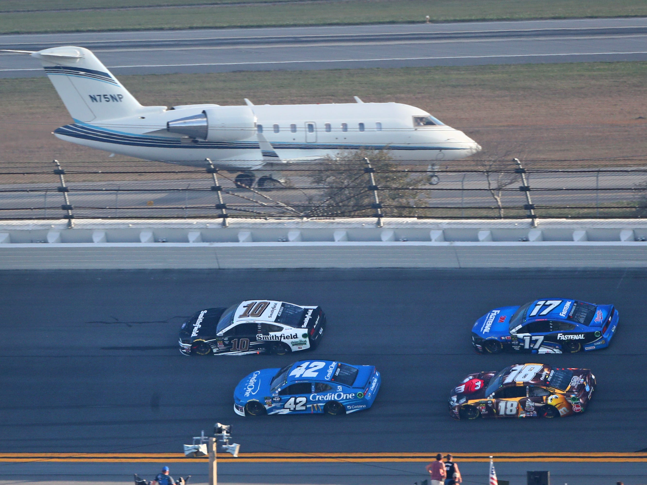 NASCAR Cup Series driver Aric Almirola (10) and Kyle Larson (42) lead Ricky Stenhouse Jr (17) and Kyle Busch (18) as a jet plane taxis at nearby airport during the Daytona 500 at Daytona International Speedway.