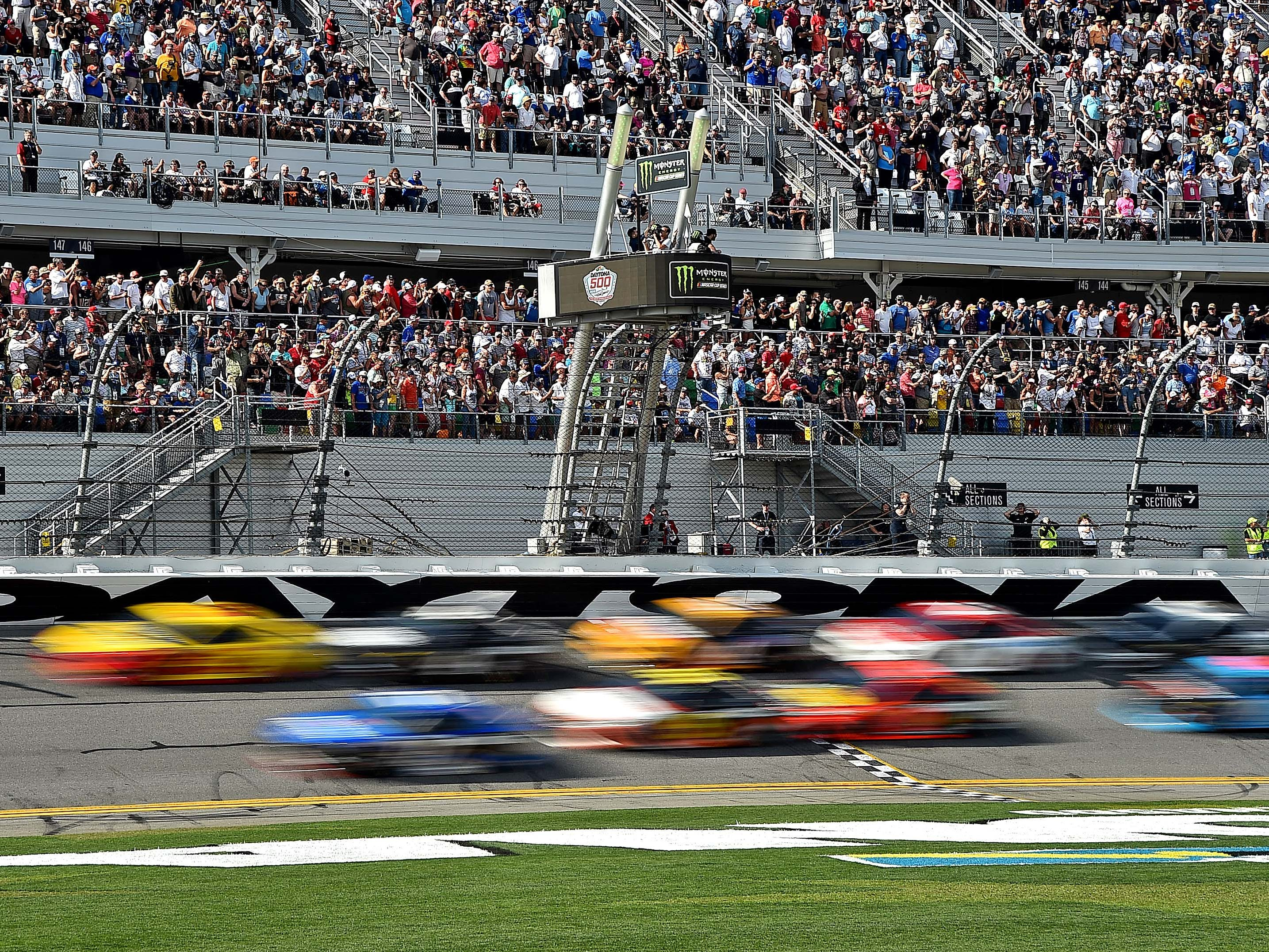 The field passes the start/finish line during the 61st Daytona 500 at Daytona International Speedway.
