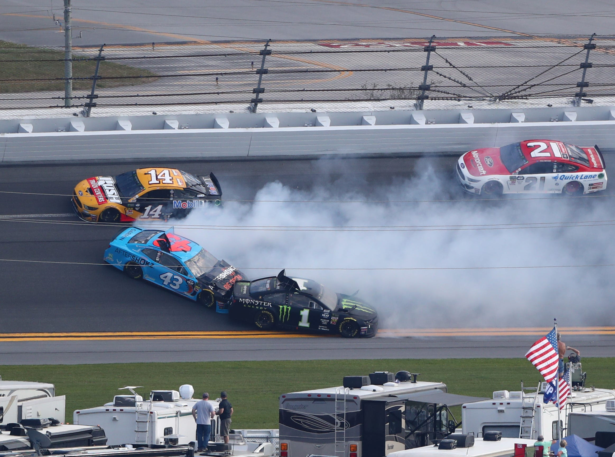 Clint Bowyer (14) and Paul Menard (21) go high as Kurt Busch (1) and Bubba Wallace (43) crash during the Daytona 500.