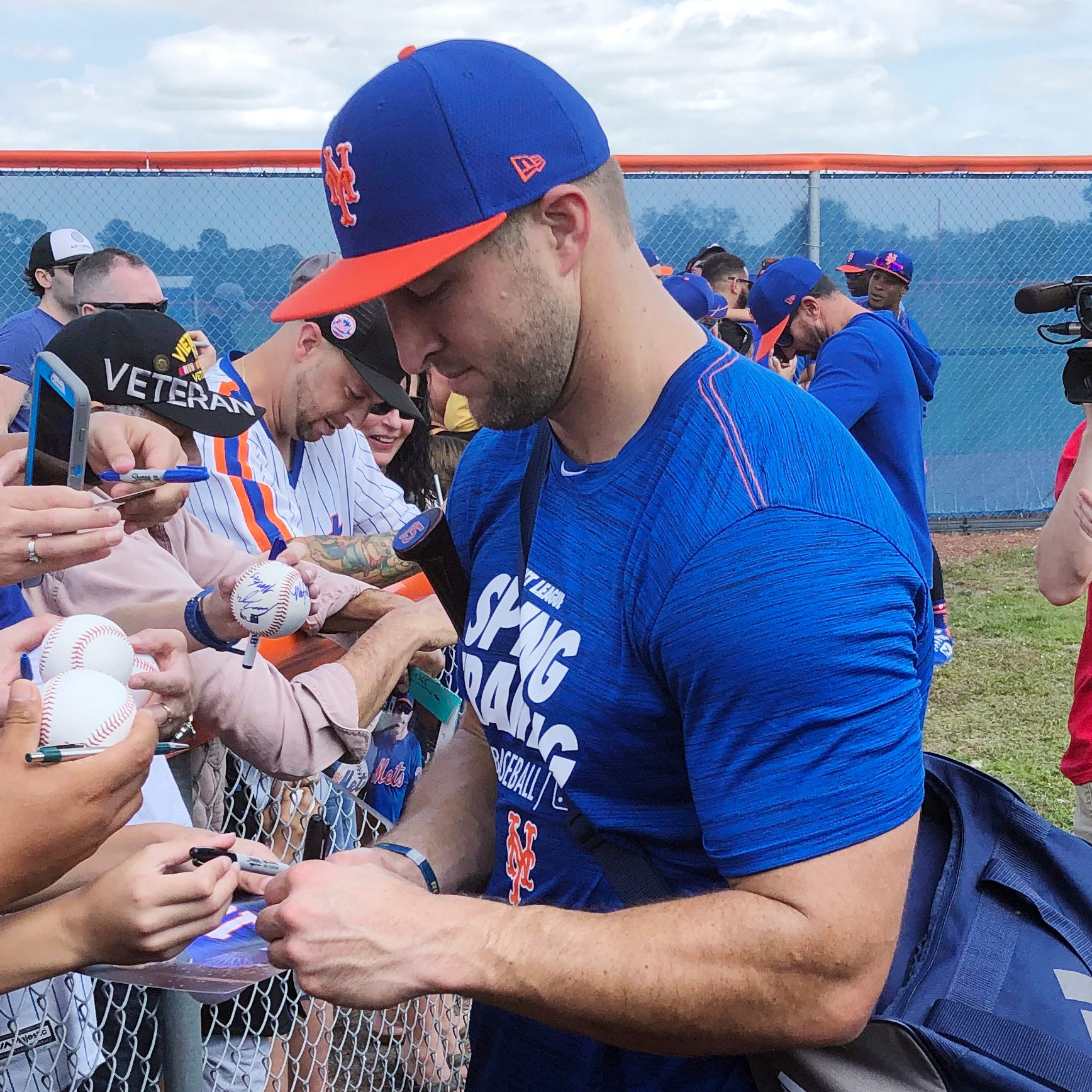 New York Mets outfielder Tim Tebow signs autographs at spring training.