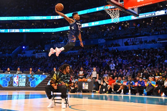Dennis Smith Jr. dunks over recording artist J. Cole in the Slam Dunk Contest.