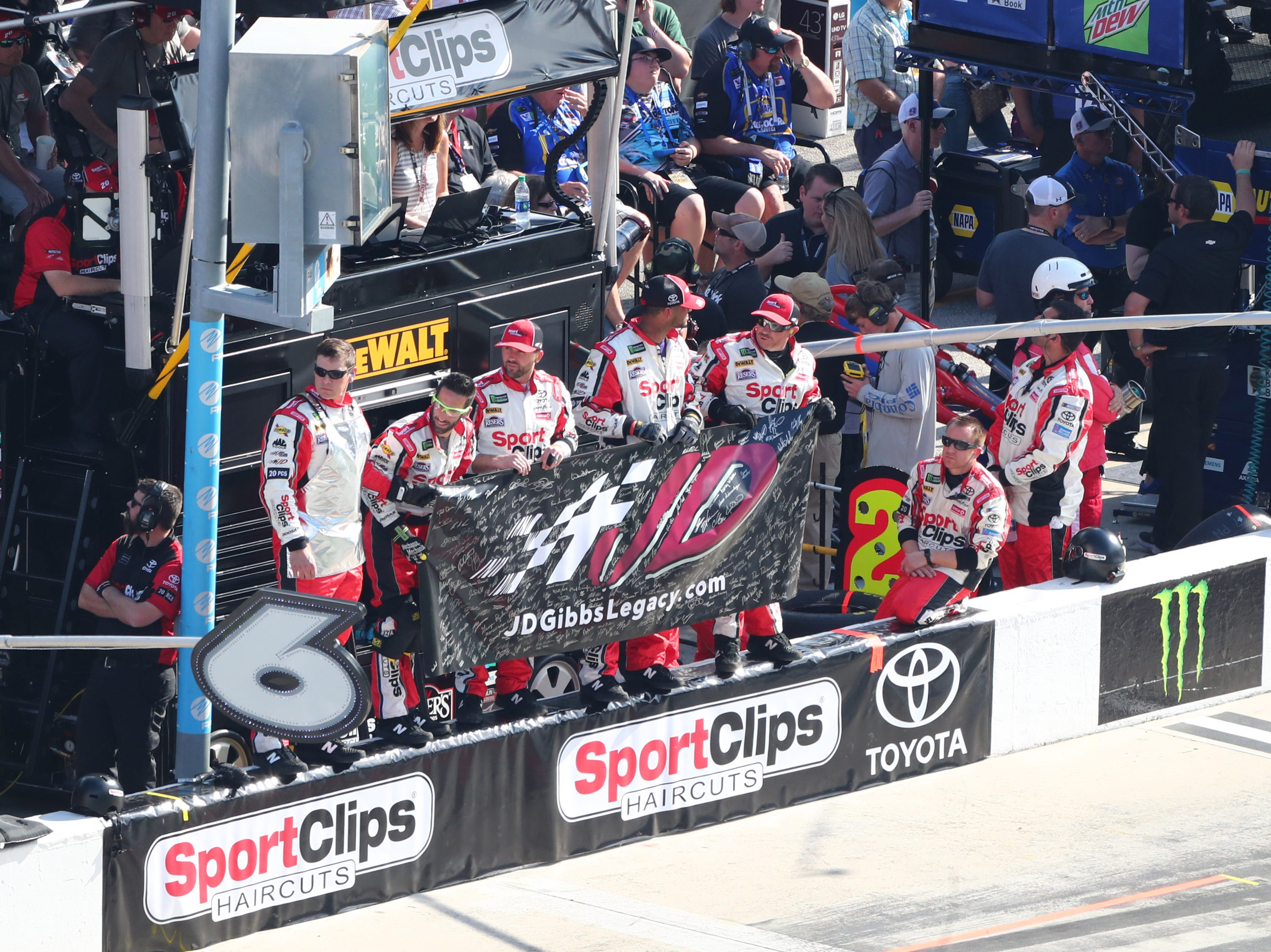 Crew members for driver Erik Jones (not pictured) stand and hold a flag in memory of J.D. Gibbs during the 11th lap of the Daytona 500.