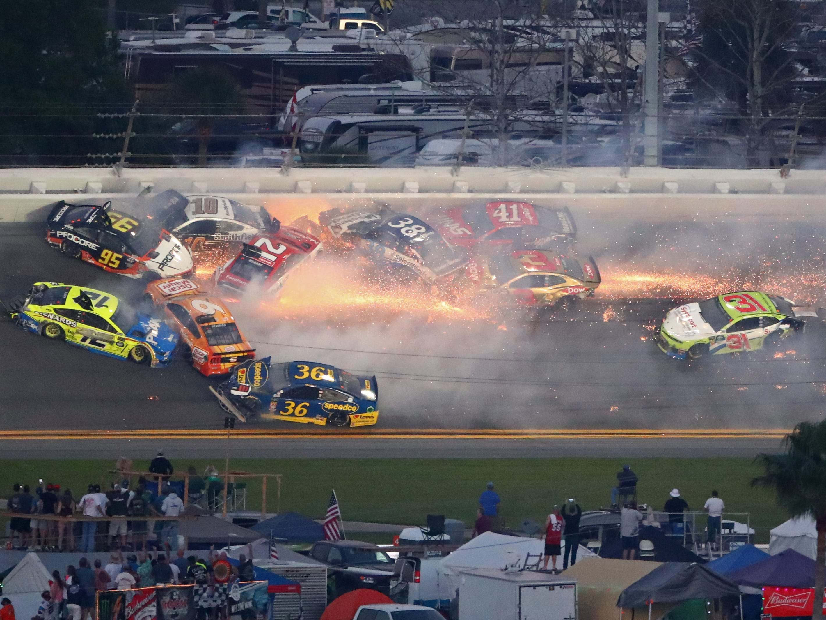 NASCAR Cup Series drivers Ryan Blaney (12), Aric Almirola (10), Paul Menard (21), NASCAR Cup Series driver David Ragan (38), Austin Dillon (3), Daniel Suarez (41), Matt Dibenedetto (95), Tyler Reddick (31),  and Ryan Newman (6) crash during the Daytona 500 at Daytona International Speedway.