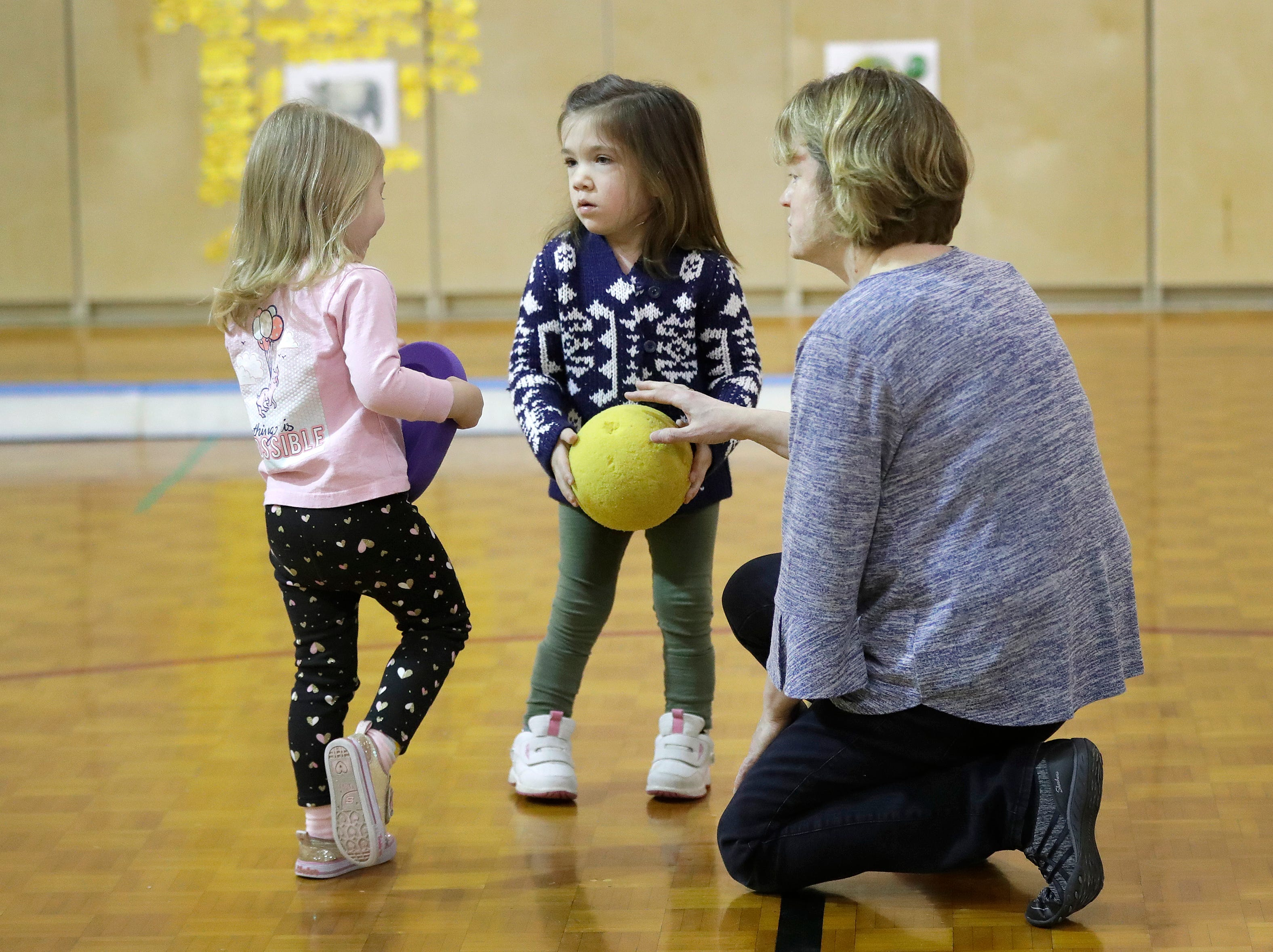Lydia Denton, 3, left, shares toys with Avi Brennan, 4, as there teacher Renee Poeschl encourages them during a gym class Monday, January 7, 2019, at the Washington School of Early Learning in Neenah, Wis. It was Avi's first day of school.Dan Powers/USA TODAY NETWORK-Wisconsin
