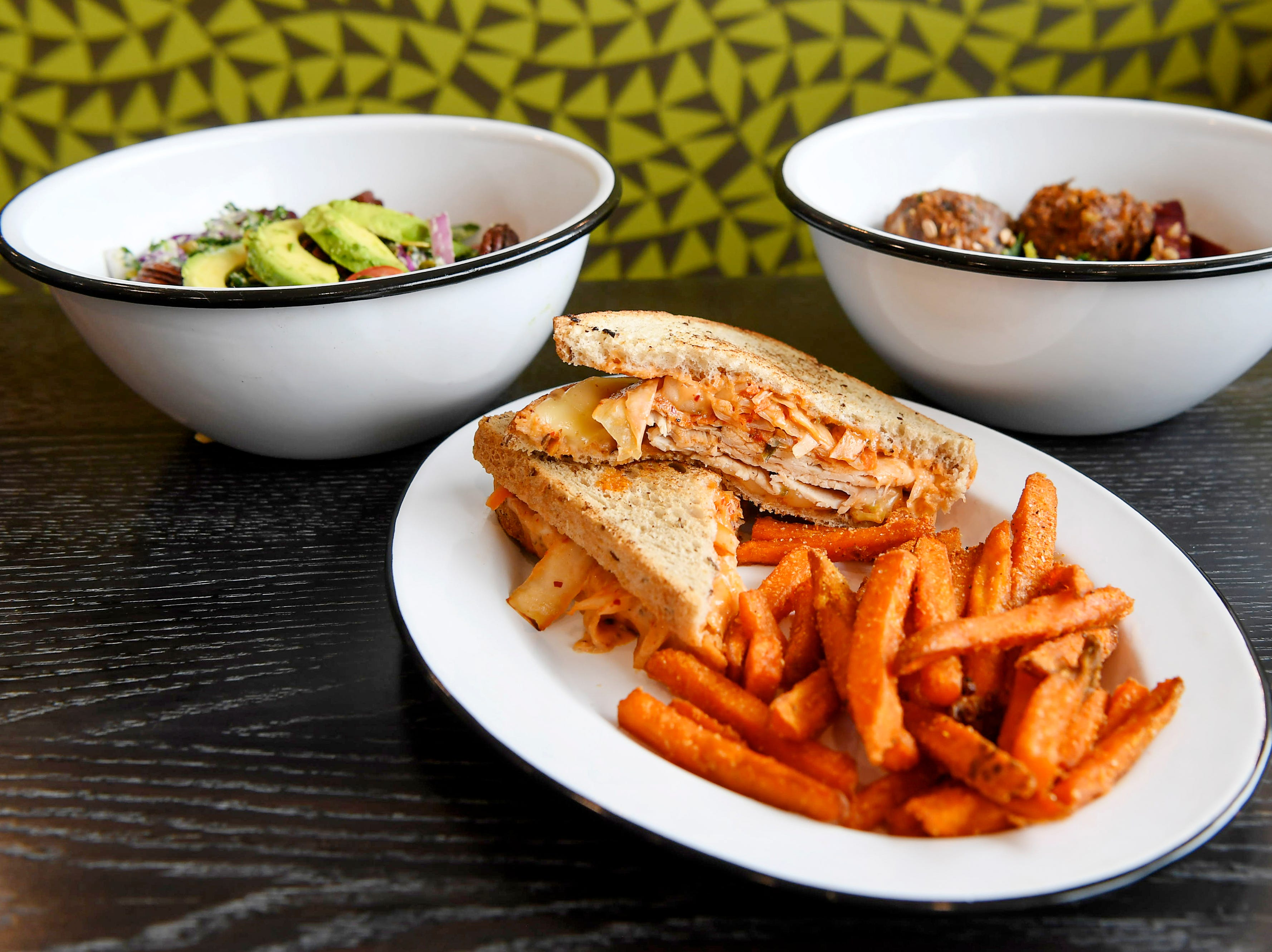 From left, Green Sage's kale salad, turkey kimchi reuben with sweet potato fries, and the Mesopotamia bowl, all offered at the cafe's new Merrimon location in North Asheville Feb. 14, 2019.