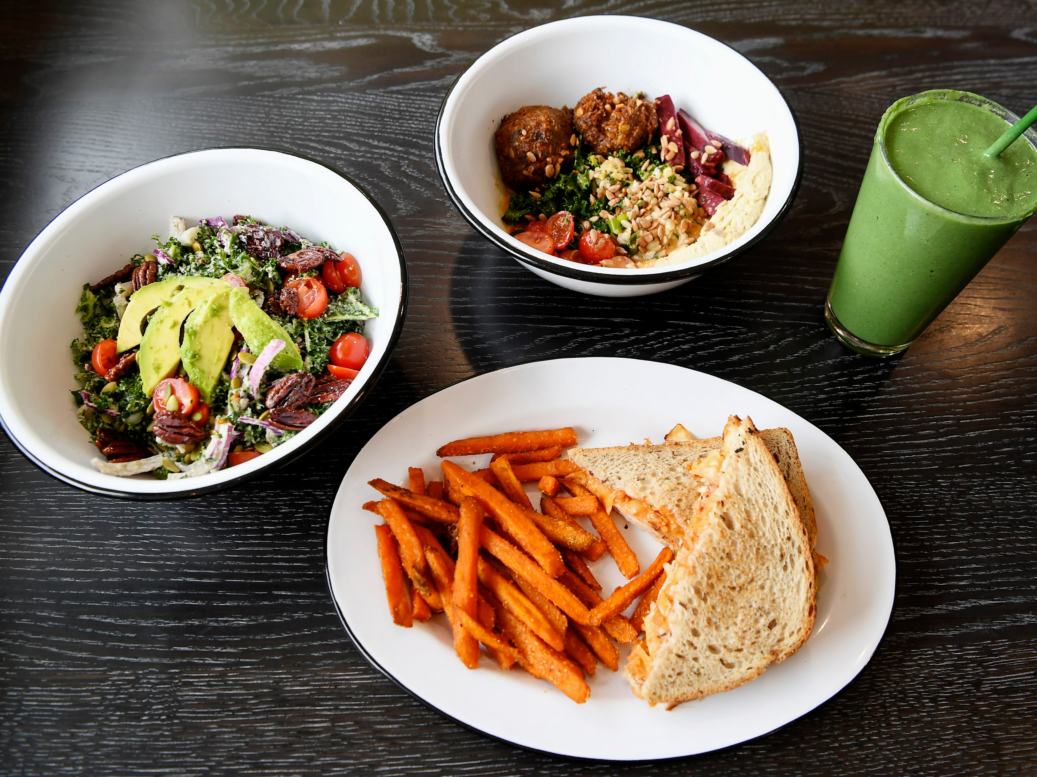 From left, Green Sage's kale salad, turkey kimchi reuben with sweet potato fries, the Mesopotamia bowl and Green Day smoothie at the cafe's new Merrimon location in North Asheville Feb. 14, 2019.