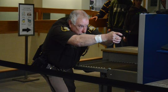 Deputy Glen Gates returns fire from an airsoft gun after two men playing the roles of assailants began shooting airsoft guns at the front door of the Calhoun County courthouse during a Monday training.
