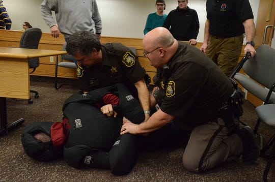 Deputies Eric Stebleton, left, and John  Dally subdue a man who played the role of a person attempting to take a gun from a deputy in the courtroom during training Monday at the Calhoun County Courthouse.