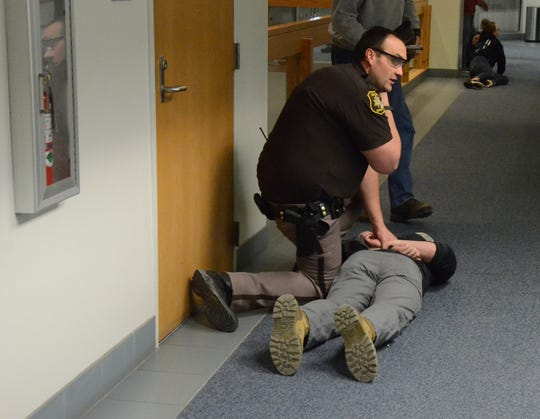 Deputy Jon Schmidt subdues a man playing the role of an active shooter during training Monday on violence scenarios in the Calhoun County Courthouse.