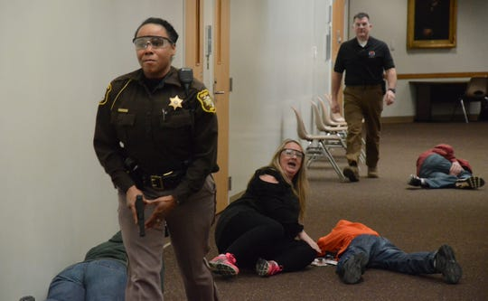 Deputy Shelanda Broughton searches the hall for a shooter during Monday's training for violence at the Calhoun County Courthouse.