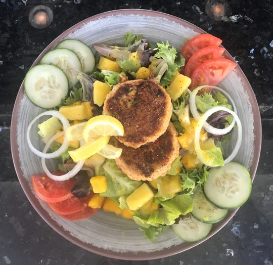 The menu at Pier 220 features lots of seafood, including this tropical salad with crabcakes.