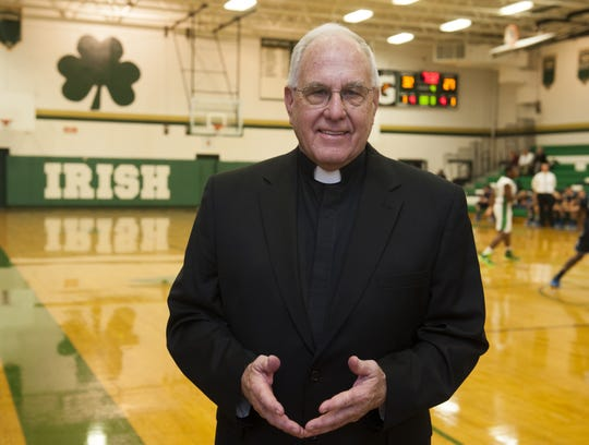 Msgr. Bob McDermott, who attended Camden Catholic High School and later taught and coached there, stands in the school's gym before a boys' basketball game in this 2014 photo.