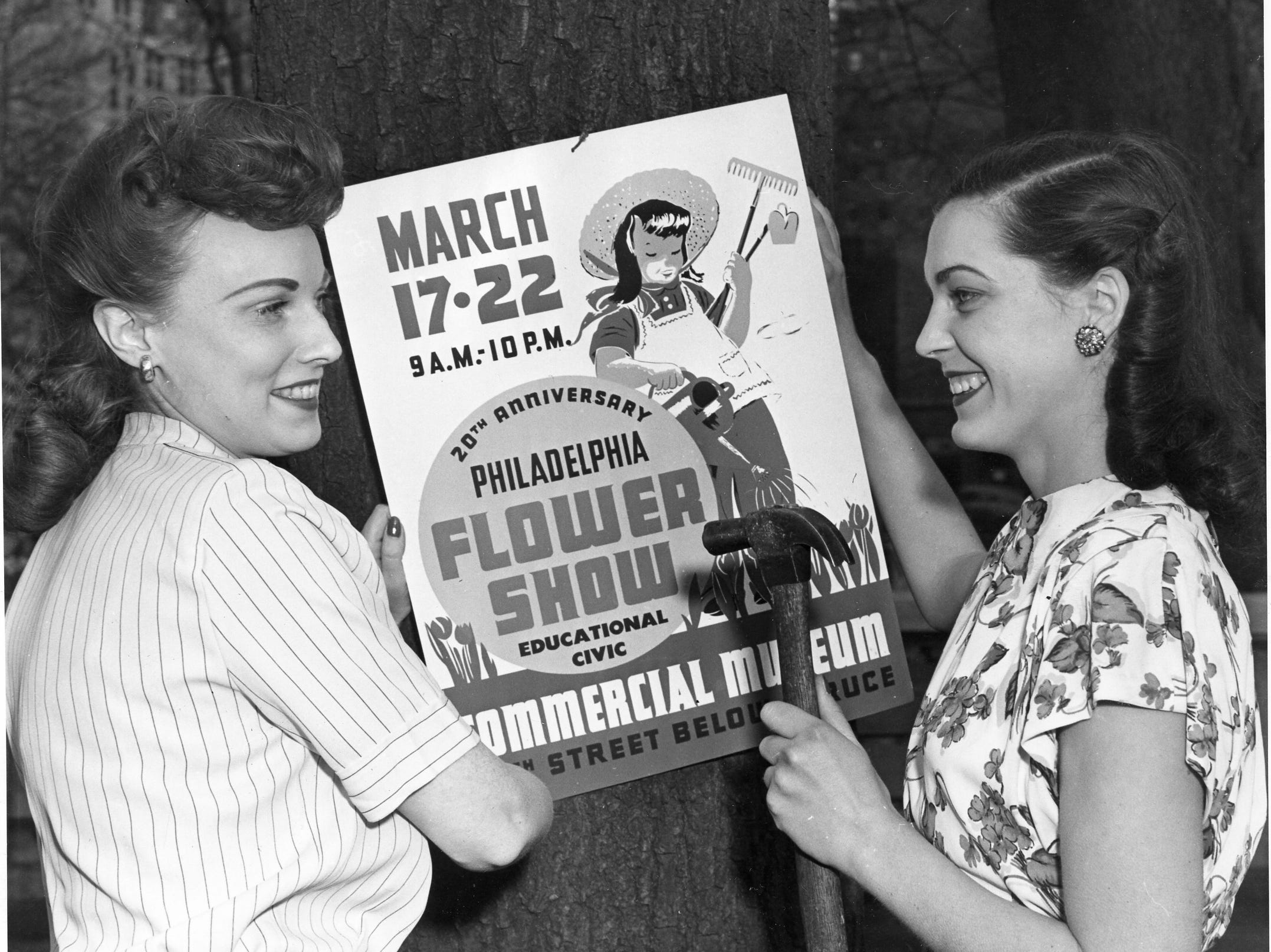 Flower show presenters hang up a poster promoting the 1947 Philadelphia Flower Show.