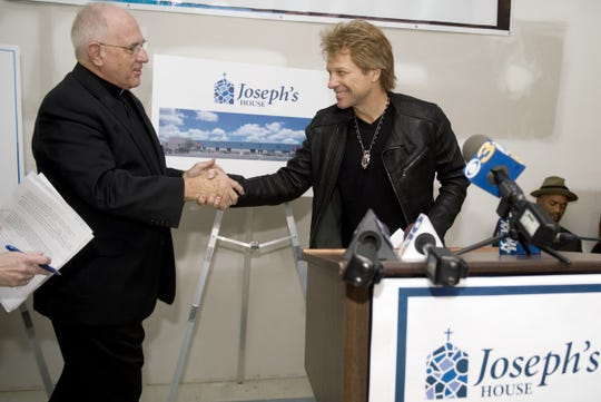 Jon Bon Jovi (right) shakes hands with Monsignor Bob McDermott of St. Joseph's Pro-Cathedral in Camden, as the rock musician visited what would become Joseph's House in Camden in 2013.