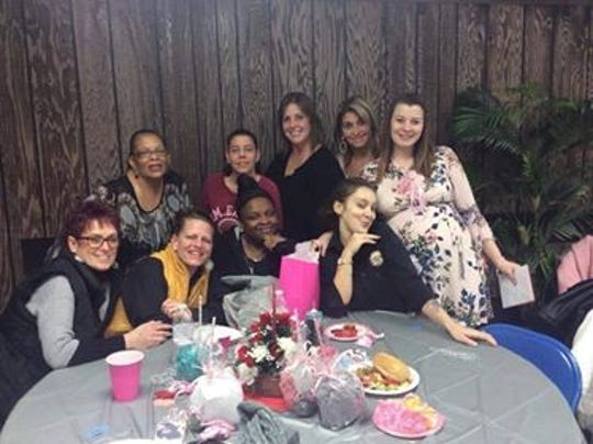 Courtney English (right) celebrates at her baby shower with friends and Lamp Post Diner co-workers. The waitress was pleasantly surprised by a $100 tip from a Voorhees police officer left with a message to enjoy her first baby.