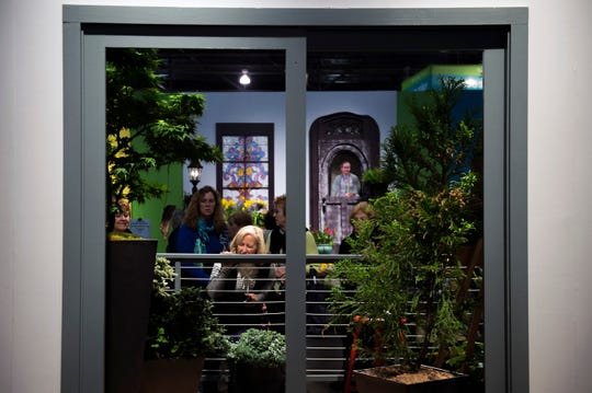 A woman gets a closer look at a patio garden on display inside the Philadelphia Flower Show Thursday, March 16, 2017 at the Convention Center in Philadelphia.