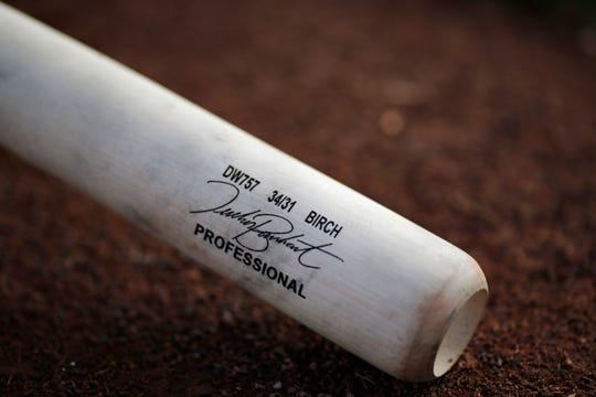 A bat belonging to Cincinnati Reds catcher Tucker Barnhart (16) lays on the field during practice at the Cincinnati Reds spring training facility in Goodyear, Ariz., on Monday, Feb. 18, 2019.