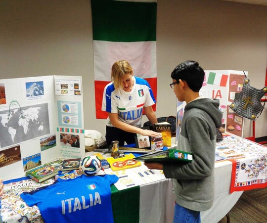 A parent volunteer shares the culture of Italy with one Indian Hill student during the Global Cultural fair at the middle school.
