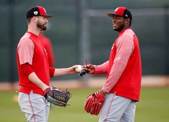 Cincinnati Reds right fielder Yasiel Puig (66) jokes with right fielder Jesse Winker (33) between reps at the Cincinnati Reds spring training facility in Goodyear, Ariz., on Monday, Feb. 18, 2019.