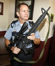 Montgomery County Sheriff Deputy Geoff Blanchard, pictured Sept. 2, 2011,  holds the weapon used by a man who shot at him during a pursuit. The weapon, a Mossburg International 702 Plinkster, was seized after the suspect wrecked on Vernon Creek Road.