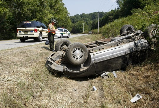A Tennessee Highway Patrol officer looks over the vehicle of a suspect who crashed on Vernon Creek Road near Highway 13 on Sept. 1, 2011. The driver shot at pursuing Montgomery County deputies.
