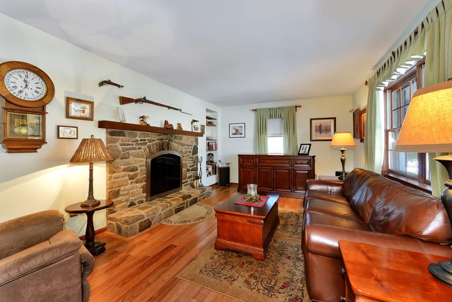 A long, paved drive lined by towering pine trees leads to a countryside property with horse facilities in Franklin Township for sale for $449,900.