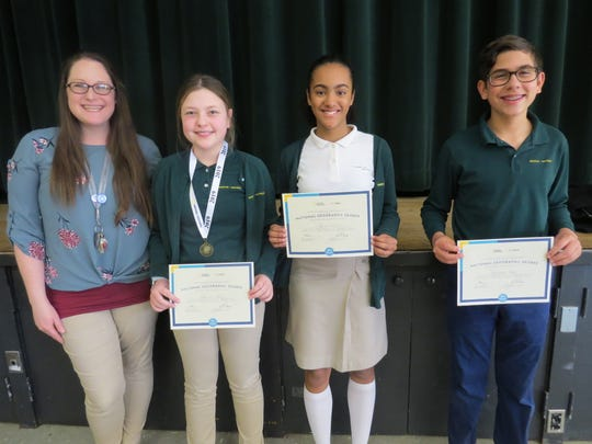 Vanessa Fang, Kayla Martel and Sebastian Tutela proudly display their certificates with Kirstin Rogers, Middle School Humanities teacher.