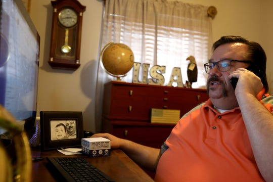 Taylor City Treasurer Ed Bourassa answers a citizen's question about city taxes from his home office  on Wednesday, February 13, 2019. Bourassa has been working from home while on disability recovering from a fall last year at a hospital.