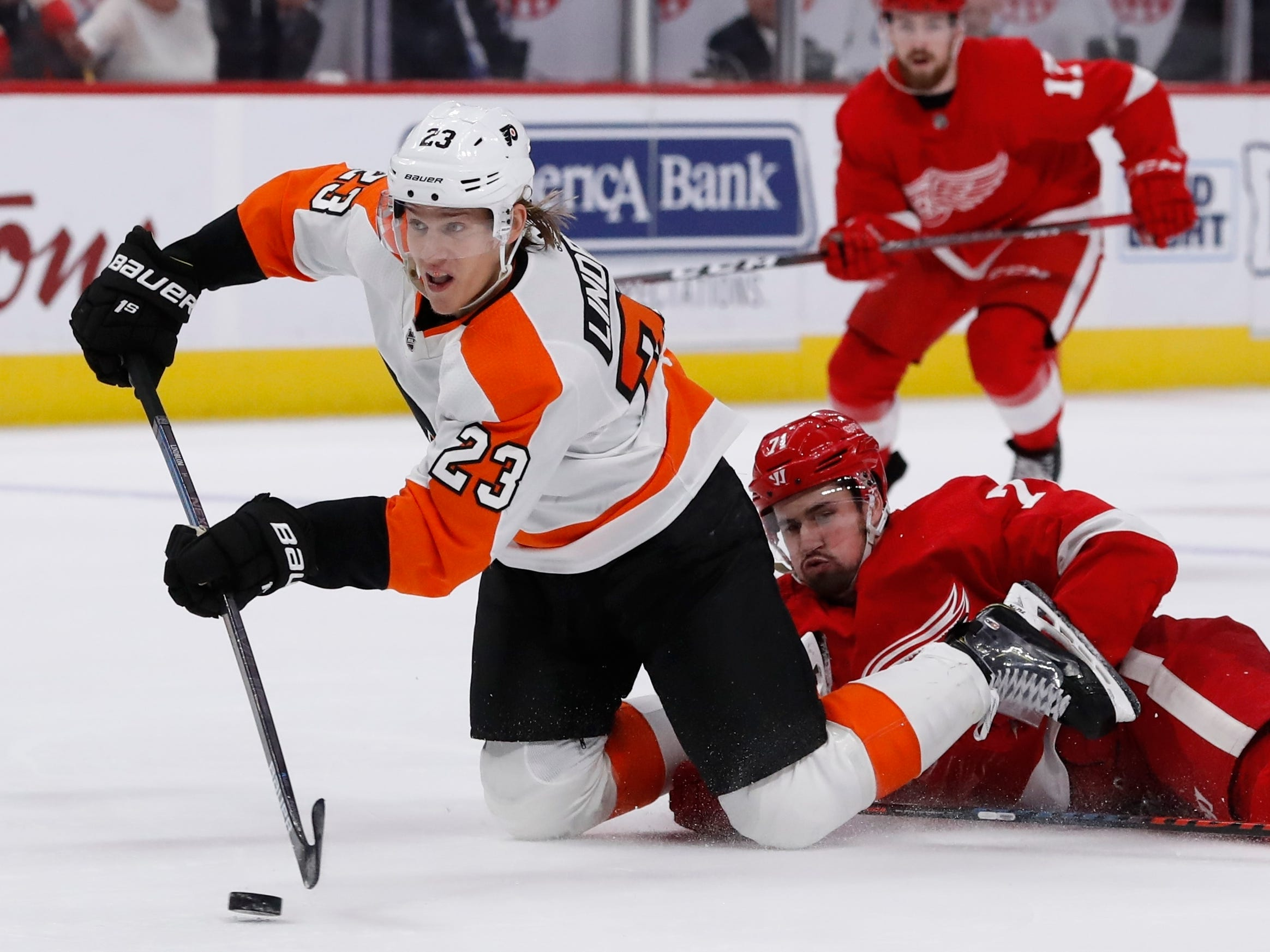 Philadelphia Flyers left wing Oskar Lindblom (23) falls in front of Red Wings center Dylan Larkin (71) and shoots at the empty net on Feb. 17, 2019, in Detroit. Lindblom scored the second of his two goals on the day.