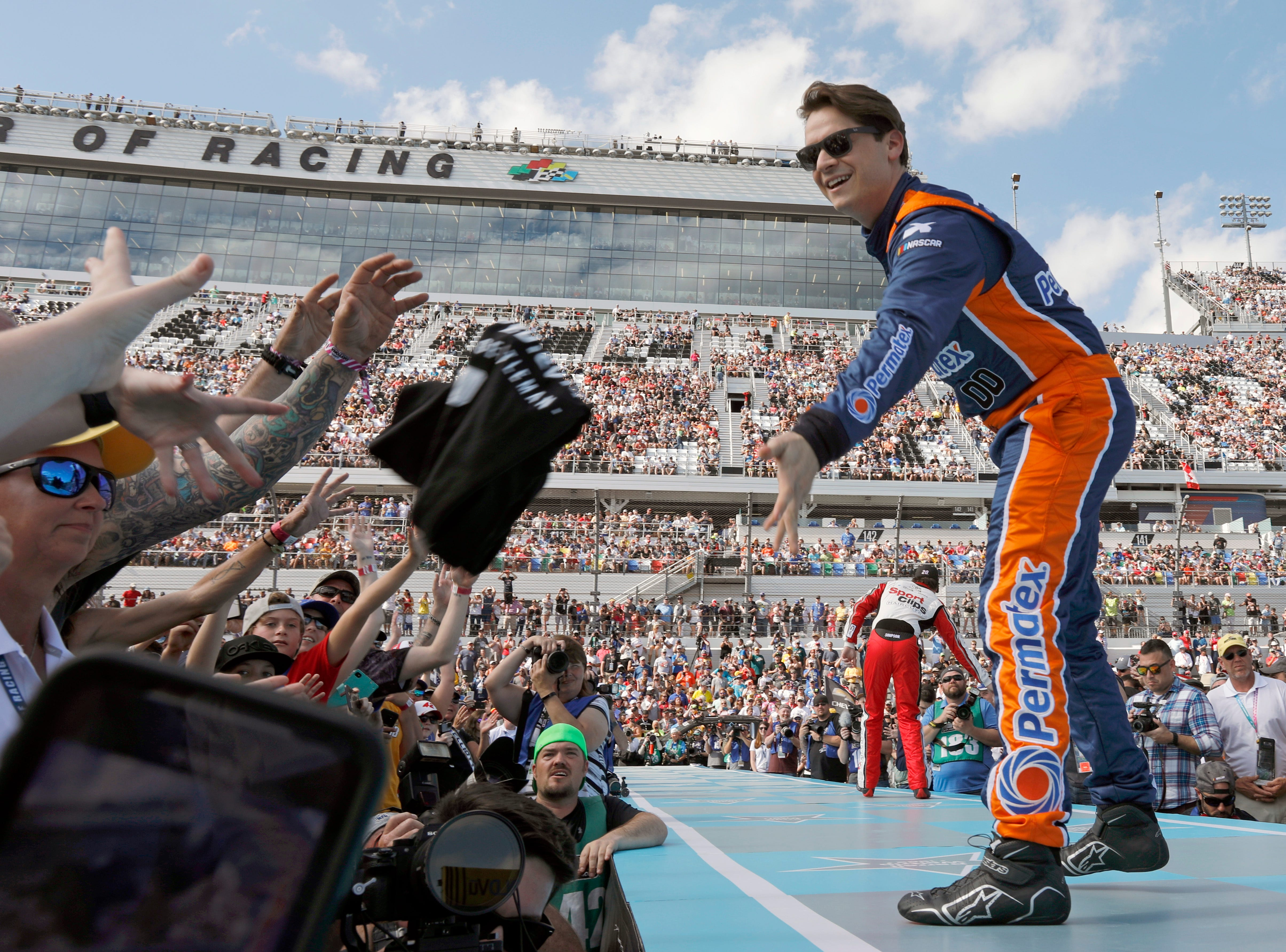 Landon Cassill, right, tosses a T-shirt to fans during driver introductions before a NASCAR Daytona 500 auto race at Daytona International Speedway.