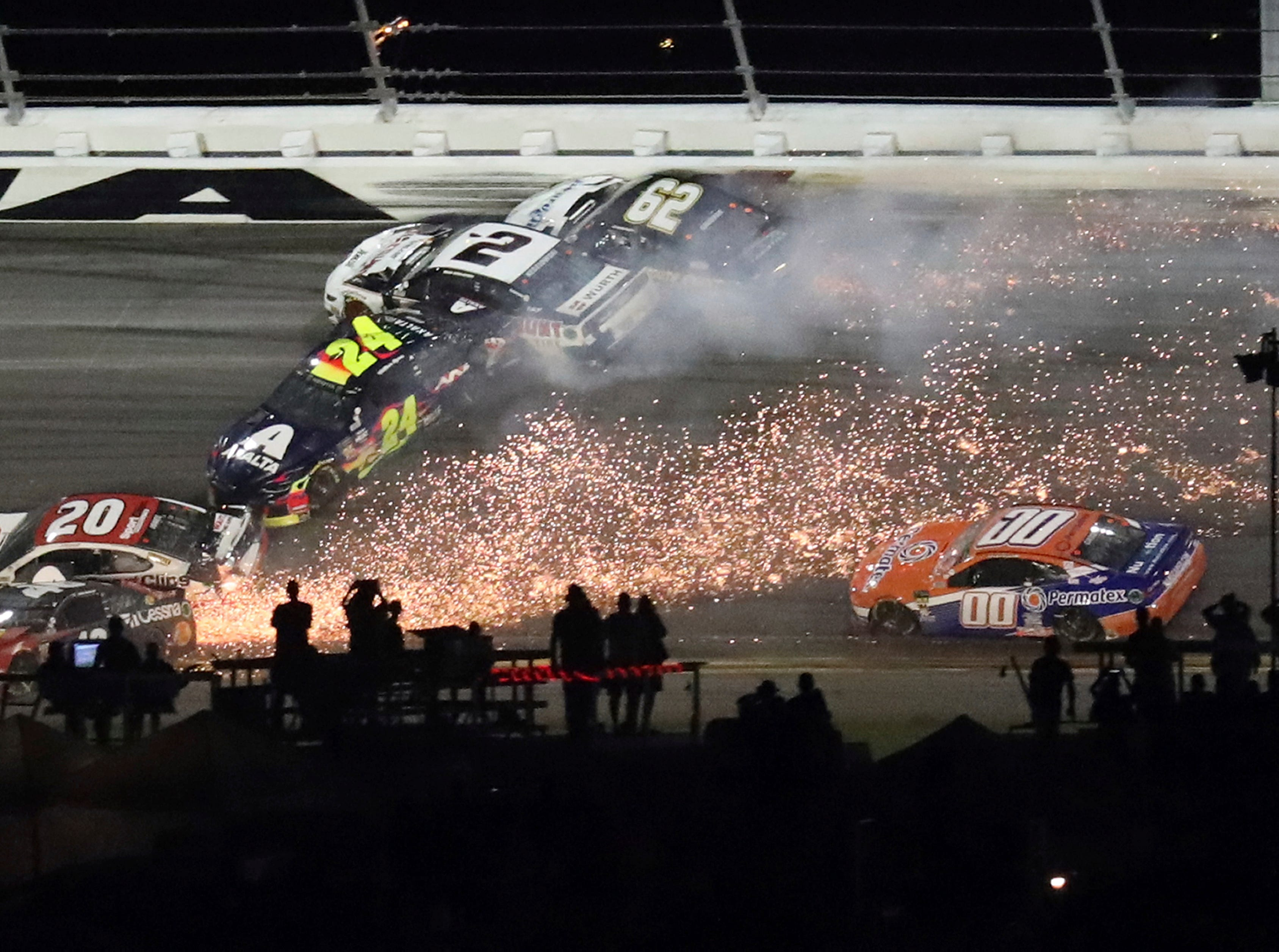 Erik Jones (20), William Byron (24), Brad Keselowski (2), and Brendan Gaughan (62) crash during a NASCAR Daytona 500 auto race.