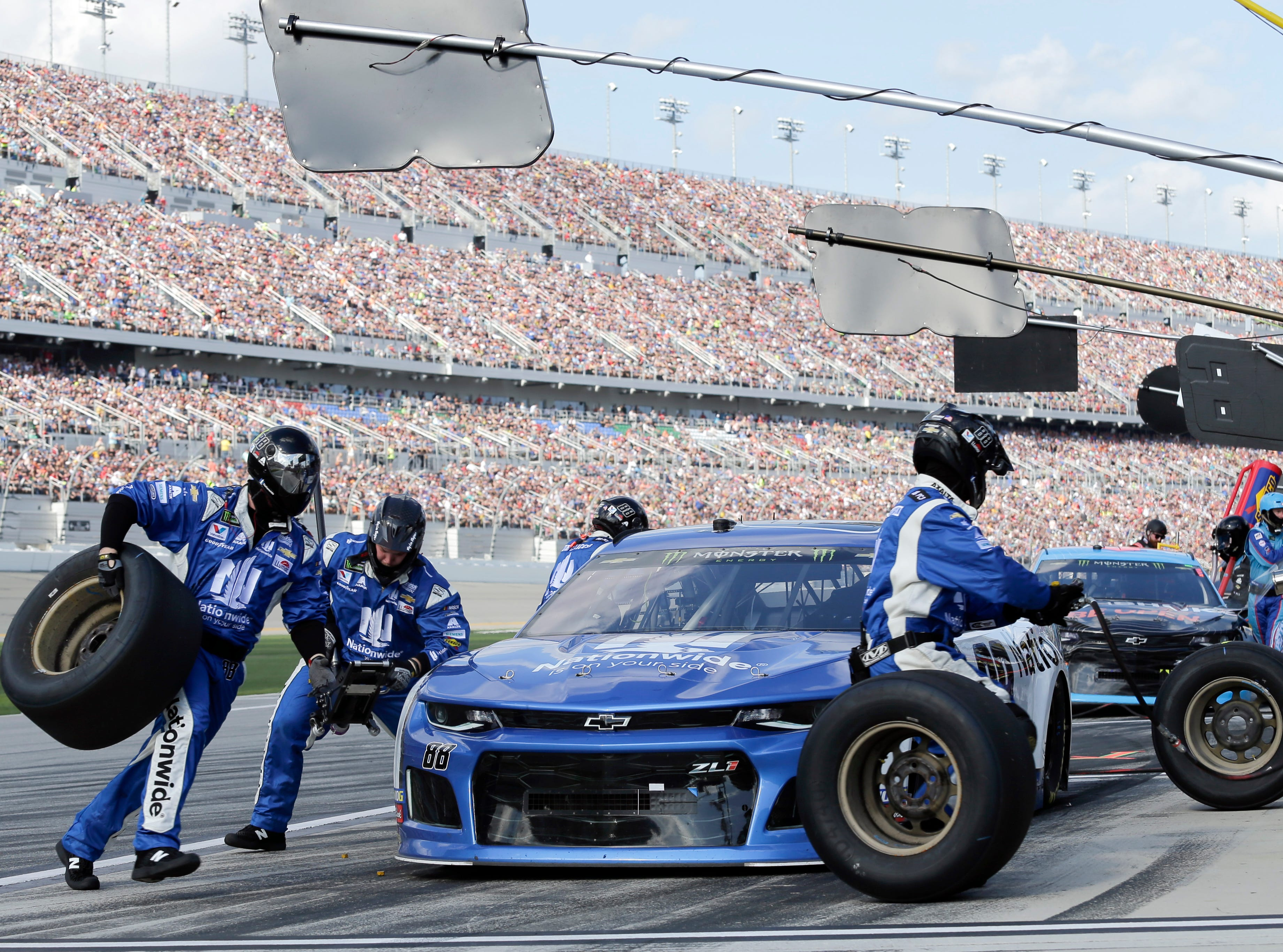 Alex Bowman's crew changes tires during a pit stop.