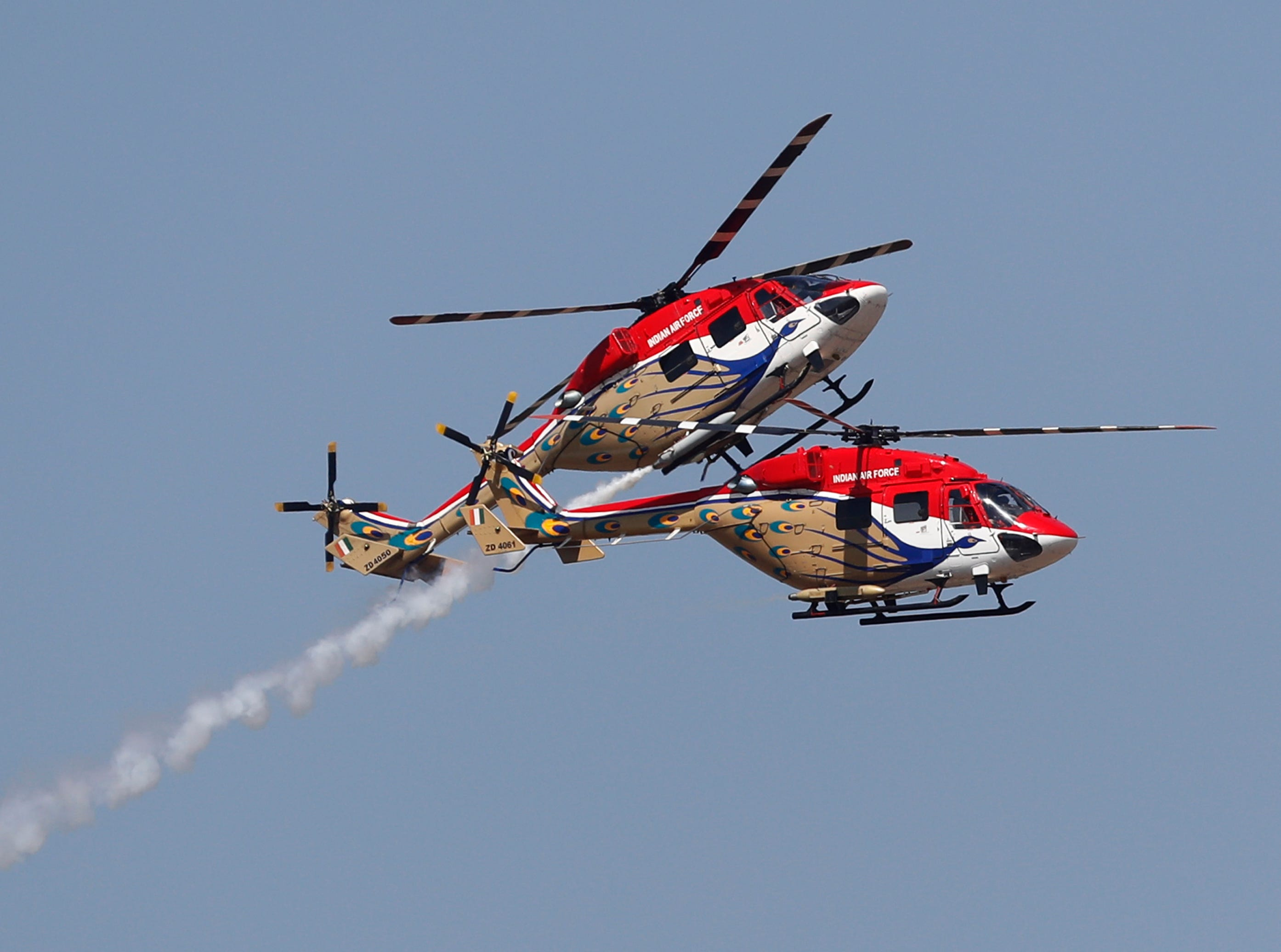 Indigenously manufactured Indian Air Force Dhruv helicopters perform aerobatic maneuvers ahead of Aero India 2019 at Yelahanka air base in Bangalore, India, Monday, Feb. 18, 2019. Aero India is a biennial event with flying demonstrations by stunt teams and militaries and commercial pavilions where aviation companies display their products and technology.