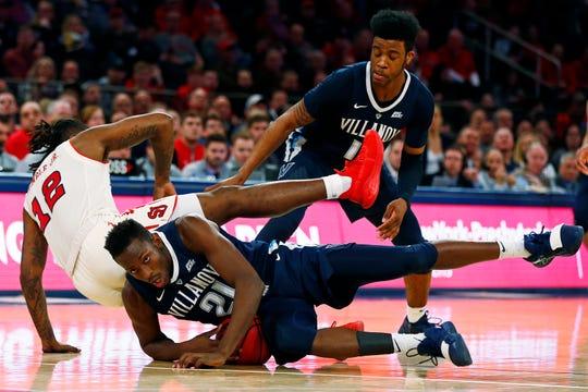 Villanova forward Dhamir Cosby-Roundtree (21) falls on a loose ball as St. John's guard Bryan Trimble Jr. (12) falls over him in front of Villanova forward Saddiq Bey.