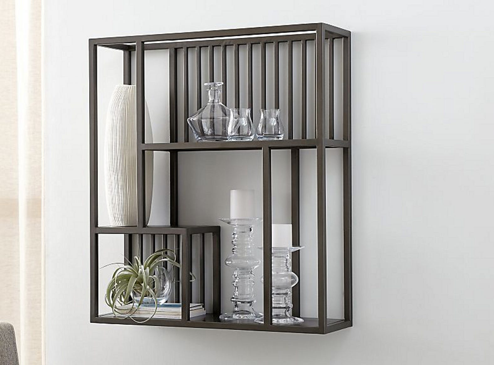 A robust linear design, the Lottie wall shelf is crafted from iron with a gunmetal finish and clear lacquer topcoat. Caged detailing and asymmetry lend style with the offset arrangement and three open shelves at varying heights.