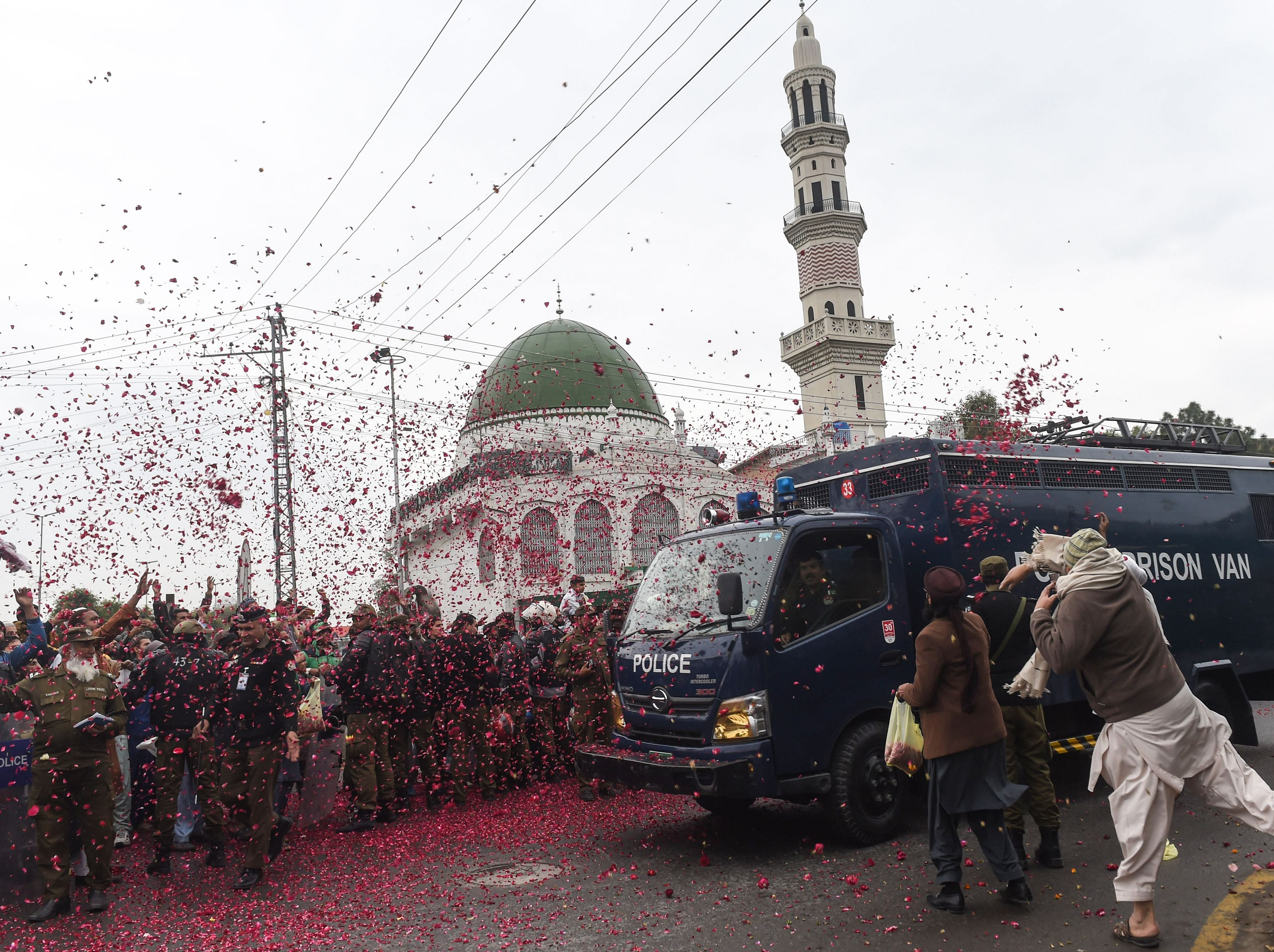 Pakistani activists of the Tehreek-Labaik Pakistan (TLP) party throw rose petals over a police van carrying the leader Khadim Hussain Rizvi as he arrives at an anti-terrorist court during a hearing in Lahore on Feb. 18, 2019, following earlier protests in opposition to the acquittal of Christian Asia Bibi from blasphemy charges.