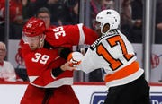 Red Wings forward Anthony Mantha (39) and  Flyers right wing Wayne Simmonds (17) fight during the first period Sunday in Detroit. (