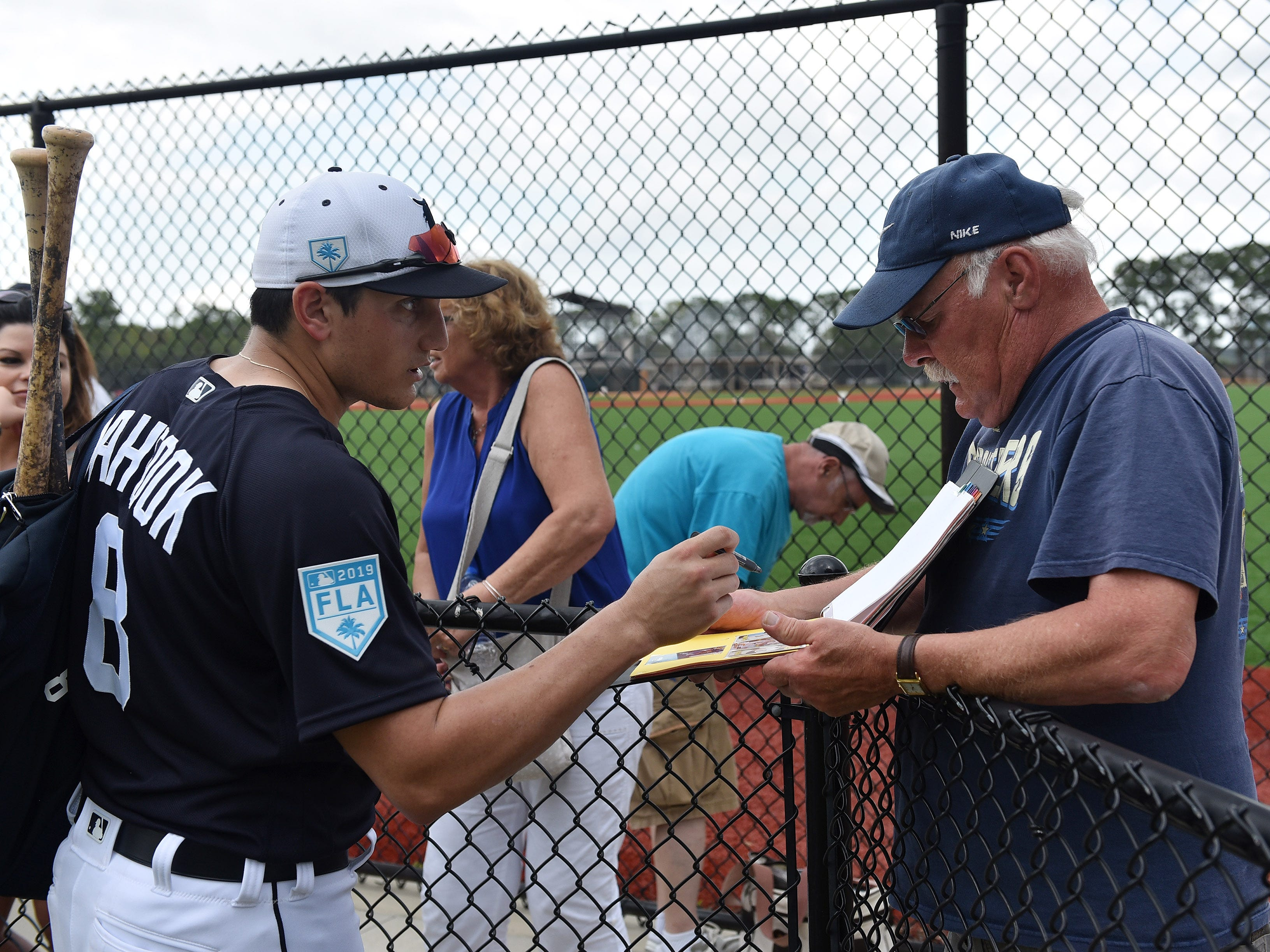 Tigers' Mikie Mahtook talks with Tom Lefchick of Warren and signs for him after the workout.