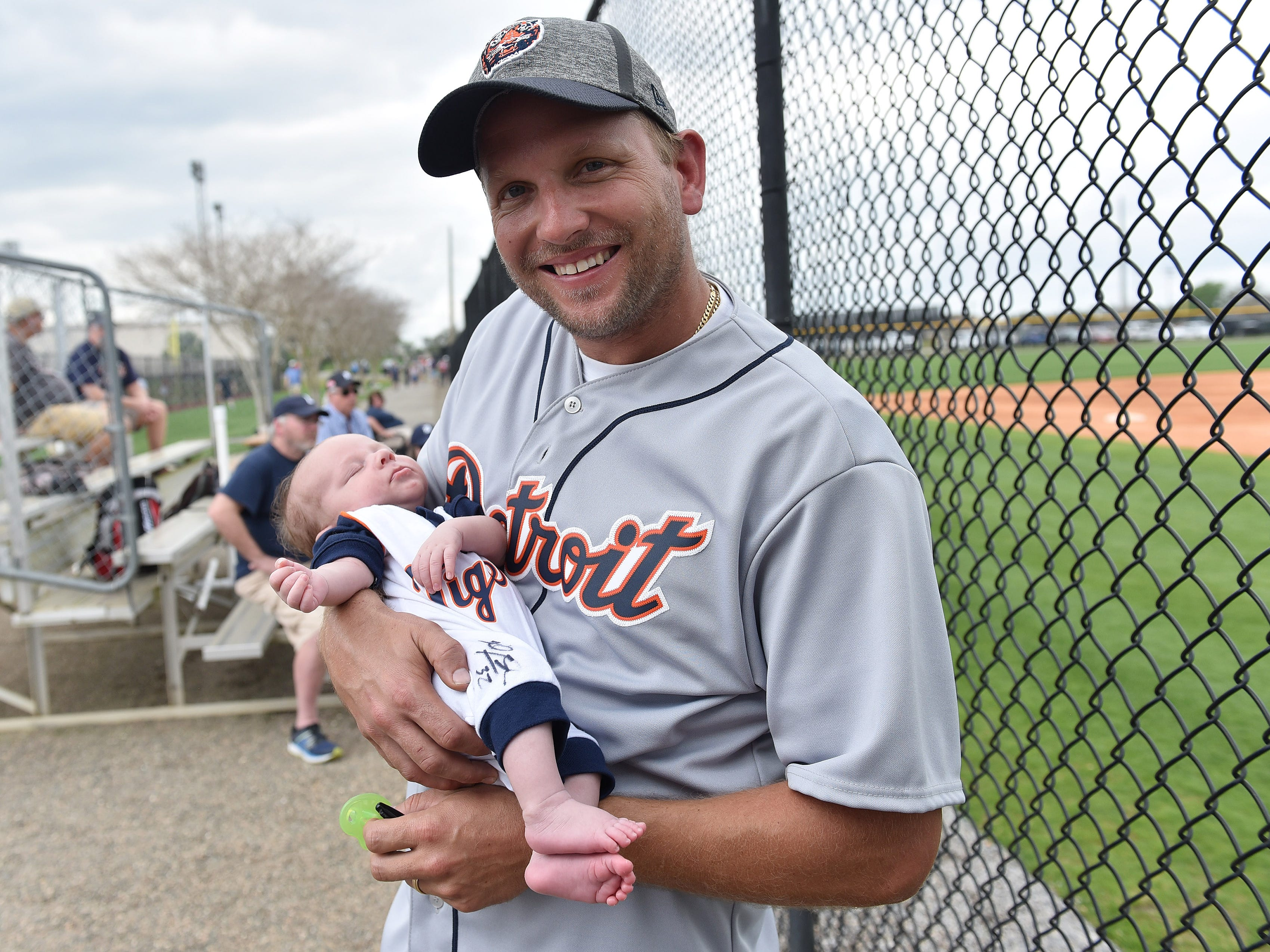 Sean Robb of Valrico, Fla. holds his son, Carter Terry Robb, who turns one month old tomorrow, at the first full squad workout. Carter's onesie was signed by Michael Fulmer. The family members are Tigers fans because in part mother's family is from Shelby Township.