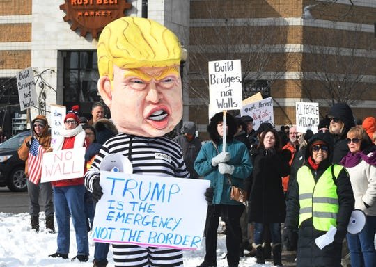 Bruce Fealk wears an oversized Donald Trump head with prison striped jumpsuit during a protest Monday on Woodward Avenue in Ferndale against President Trump's declaration of a national emergency .