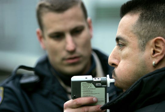 California Highway Patrol officer Mark Rossetti administers a Breathalizer test to a man at a sobriety checkpoint December 26, 2004 in San Francisco, California.