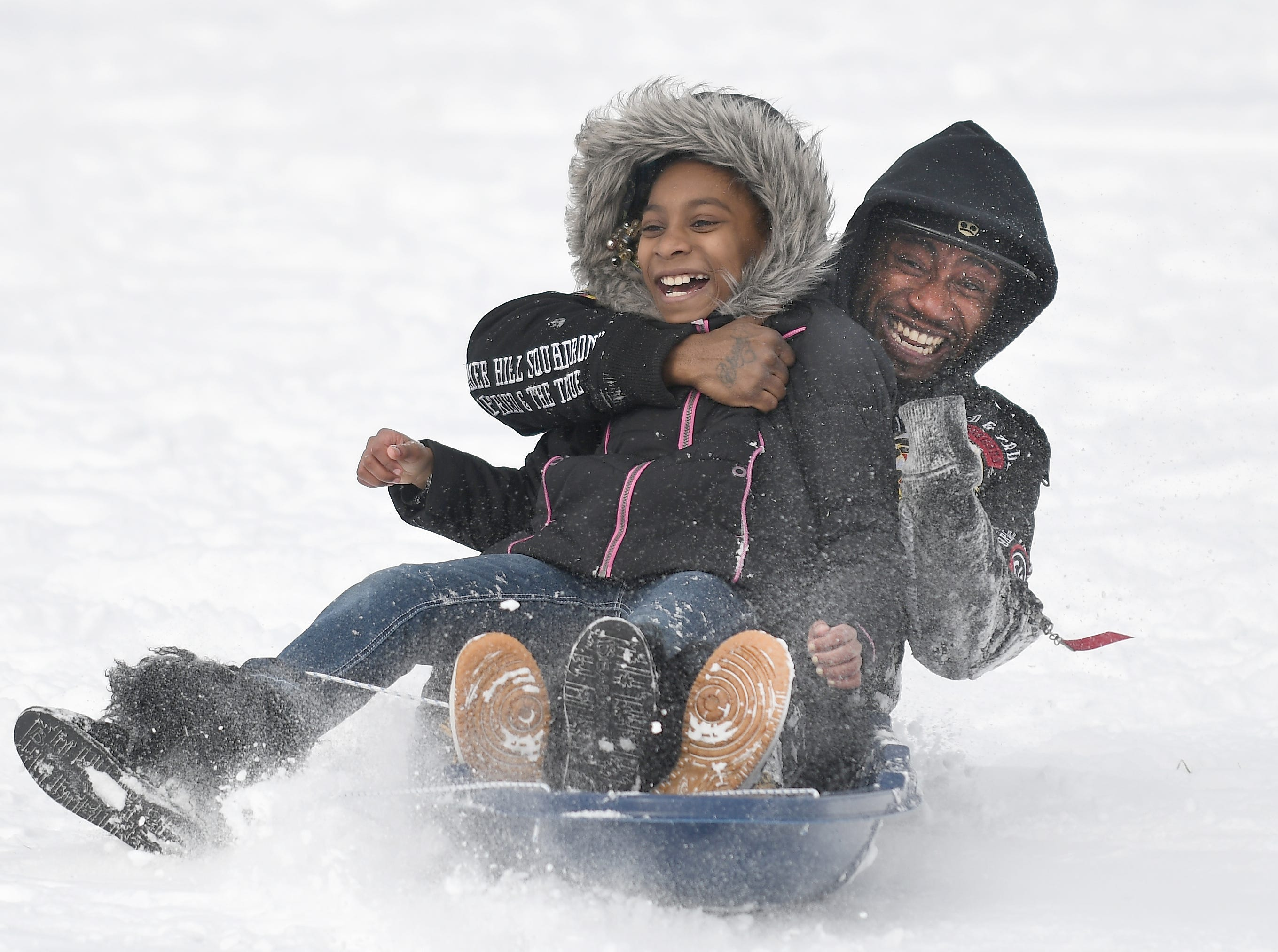 Lejai Criter, 9, and Ryland Criter slide backward down the hill at Madison Heights Community Park in Madison Heights on Monday, Feb. 18, 2019.