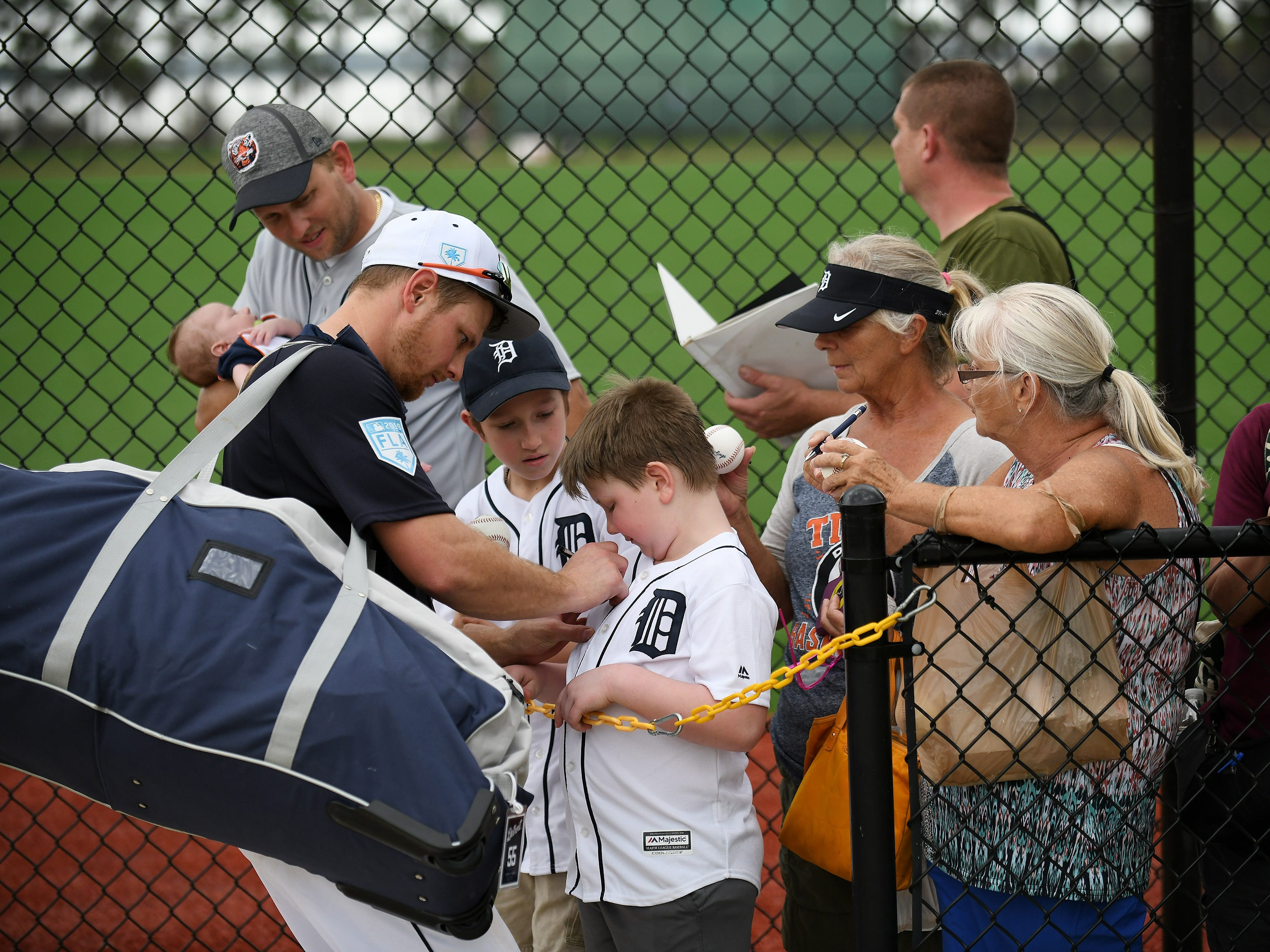 Tigers catcher John Hicks signs the jersey of Landon Simunic, 8, of Shelby Township after the workout.