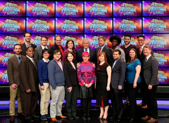 """This image released by Jeopardy Productions, Inc. shows, front row from left, Brad Rutter, Colby Burnett, Alan Lin, Seth Wilson, Larissa Kelly, Monica Thieu, Pam Mueller, Matt Jackson, Jennifer Giles and Ken Jennings, back row from left, Ben Ingram,  Roger Craig, David Madden, Julia Collins, host Alex Trebek, Austin Rogers, Leonard Cooper, Alex Jacob and Buzzy Cohen on the set of the game show """"Jeopardy!"""""""
