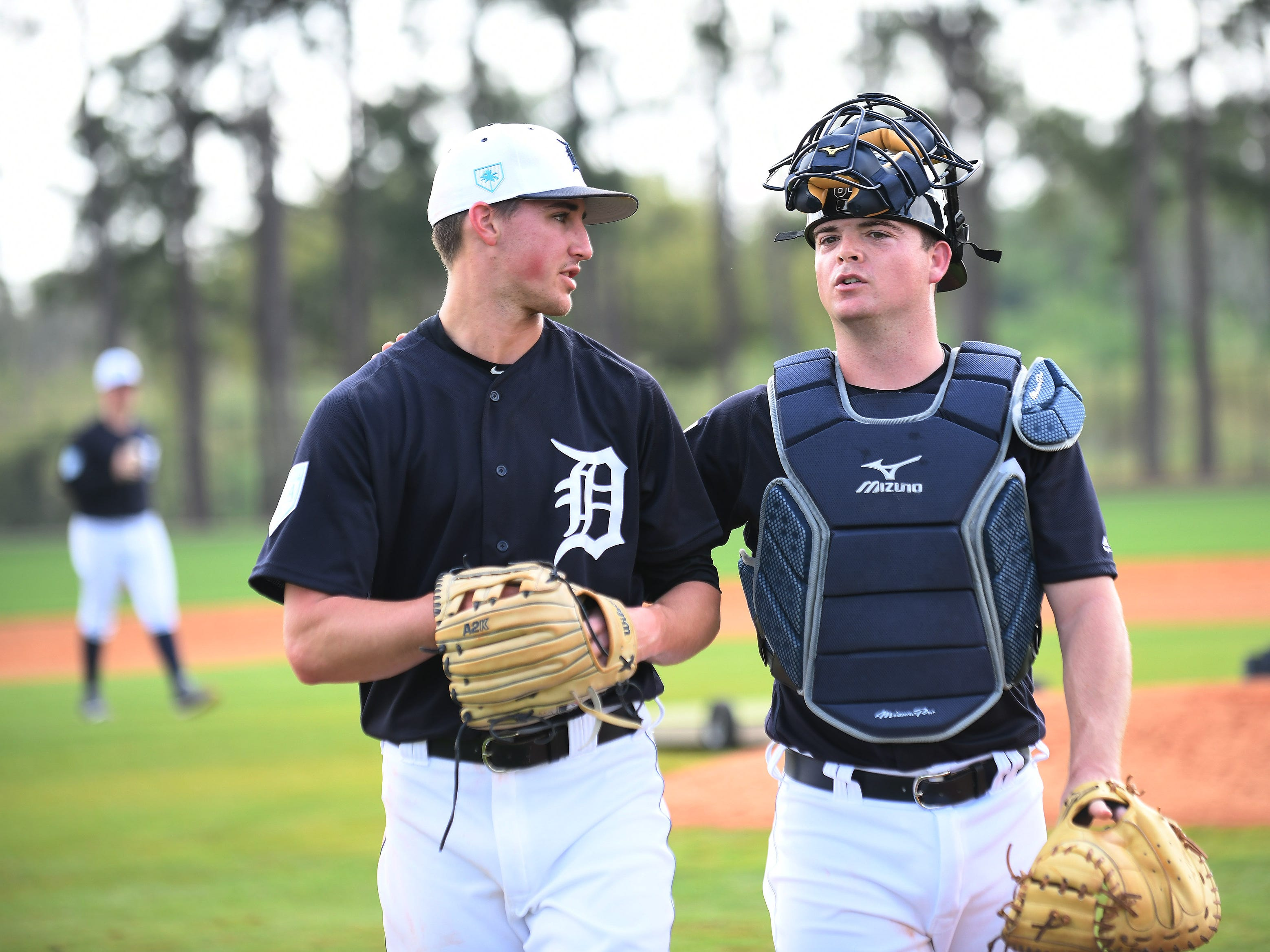Non-roster catcher Jake Rogers, right, talks with pitcher Zac Reininger, left, after Reininger pitched live batting practice.
