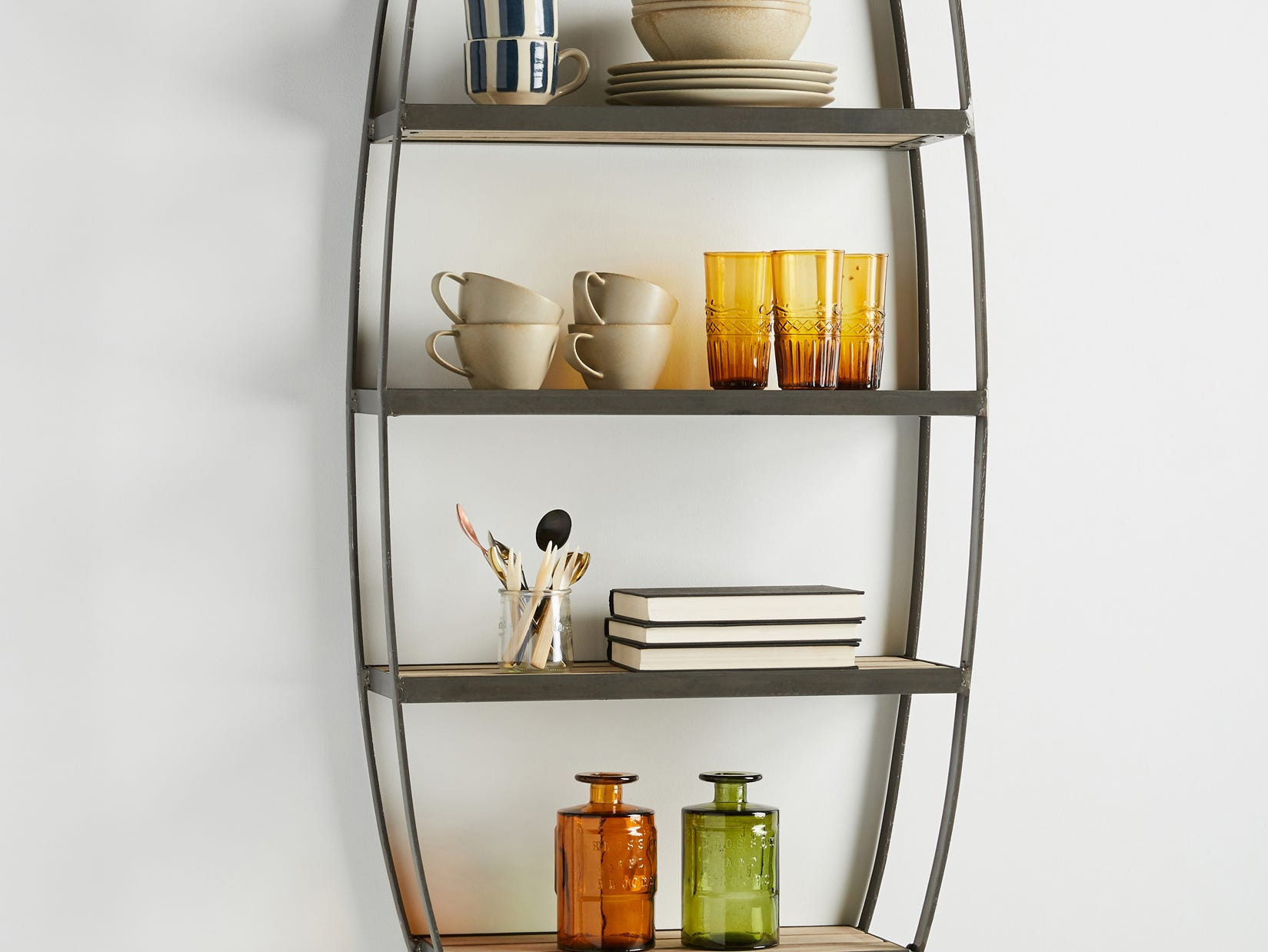 Reminiscent of curio cabinets, this paulownia wood wall-hung shelving is held in an exaggerated oval frame hand-crafted from raw iron. Design your own cabinet of curiosities on five tiers. The piece is 60 3/4 inches tall and 22 1/4 inches wide, with an 8-inch projection.